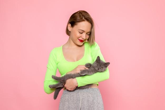 緑のシャツとかわいい灰色の子猫を保持している灰色のスカートの若い女性