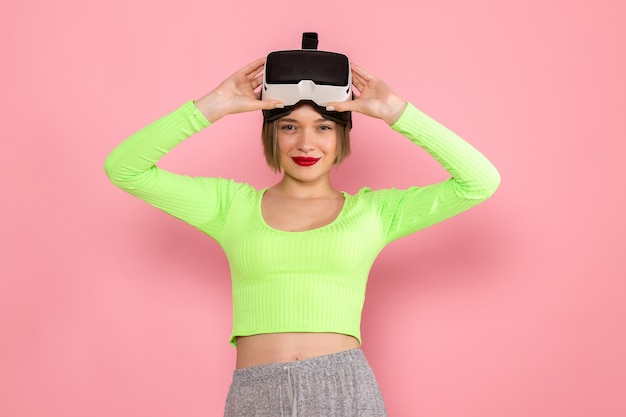 緑のシャツと灰色のスカートの仮想現実を試して笑顔の若い女性
