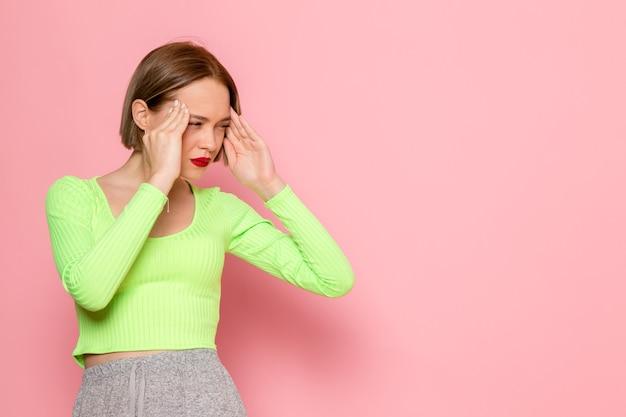 緑のシャツと灰色のズボンの痛みで頭を抱えた若い女性