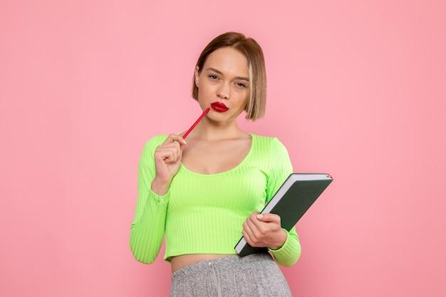 緑のシャツと赤のペンとコピーブックでポーズをとって灰色のズボンの若い女性