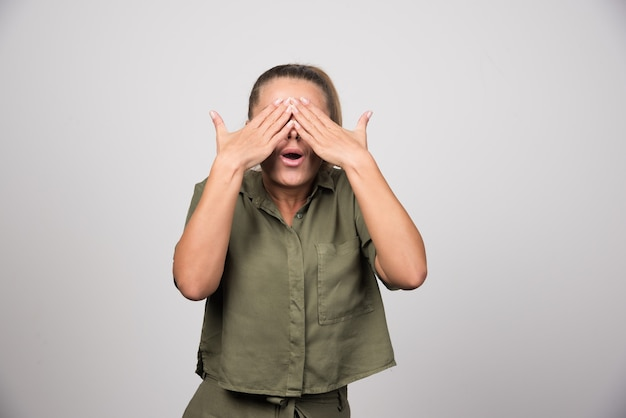 Молодая женщина в зеленой рубашке, закрыла глаза.