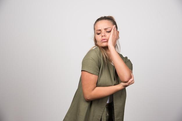 Молодая женщина в зеленой рубашке с зубной болью.