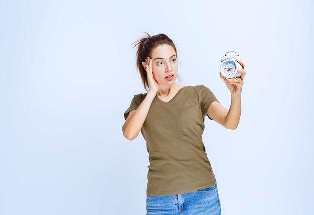 目覚まし時計を保持し、混乱しているように見える緑色のシャツを着た若い女性