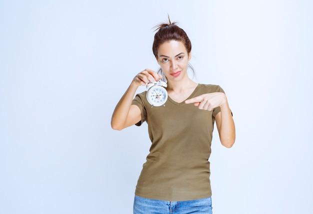 Молодая женщина в зеленой рубашке держит будильник
