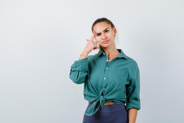 額に指を保ち、真剣に見える緑色のシャツを着た若い女性、正面図。