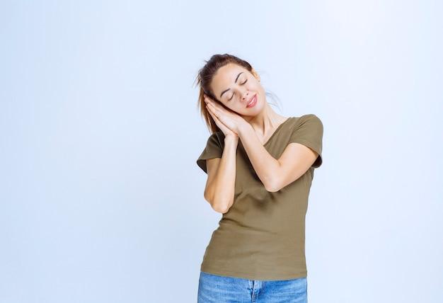 Молодая женщина в зеленой рубашке выглядит сонной и уставшей