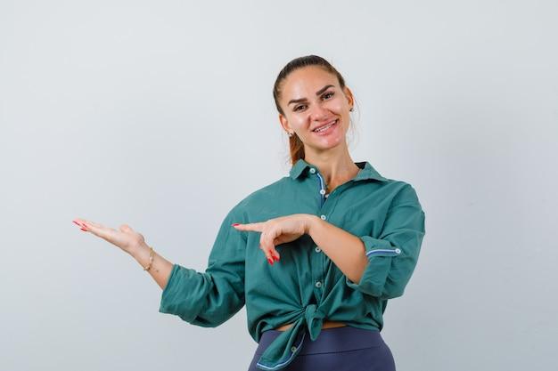 彼女の手のひらを指している緑のシャツを着た若い女性は脇に広がり、陽気に見える、正面図。
