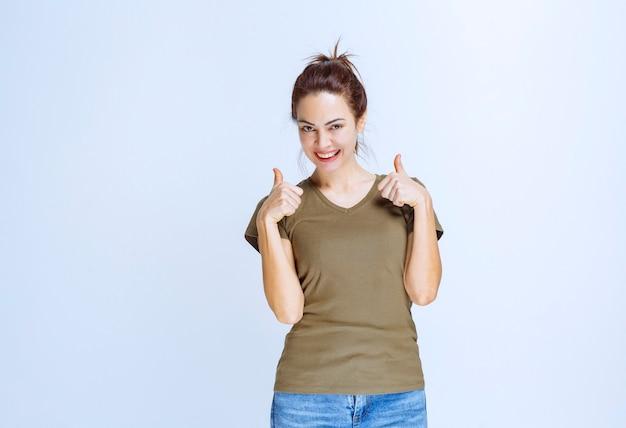 Молодая женщина в зеленой рубашке показывает знак удовольствия