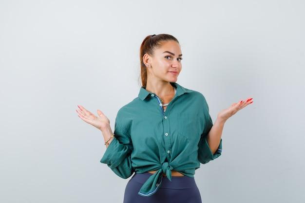 無力なジェスチャーを示し、混乱しているように見える緑色のシャツを着た若い女性、正面図。