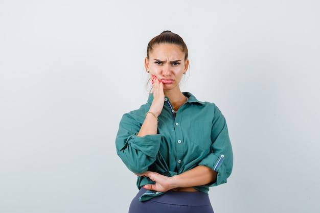 歯痛に苦しんでいる緑のシャツを着た若い女性と動揺して、正面図。