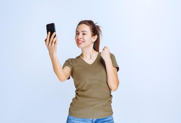 Молодая женщина в зеленой рубашке делает селфи и выглядит мотивированной