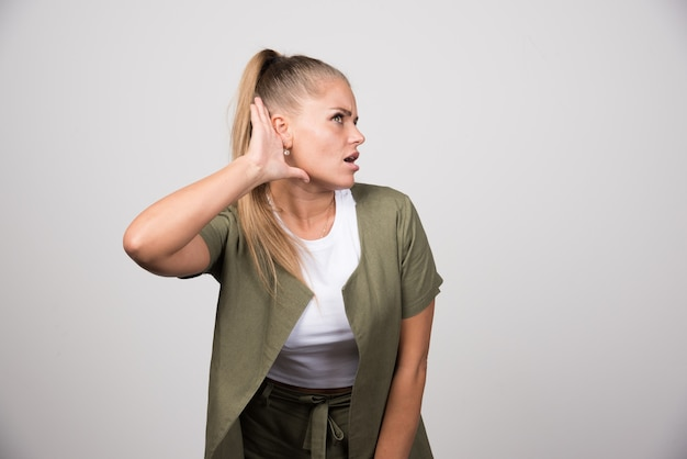듣고하려고 녹색 셔츠에 젊은 여자.