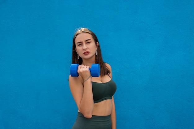 青に分離された青いダンベルを保持している緑のスポーツ布の若い女性。健康と美容のライフスタイル