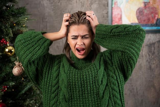 그녀의 머리를 잡고 녹색 스웨터에 젊은 여자