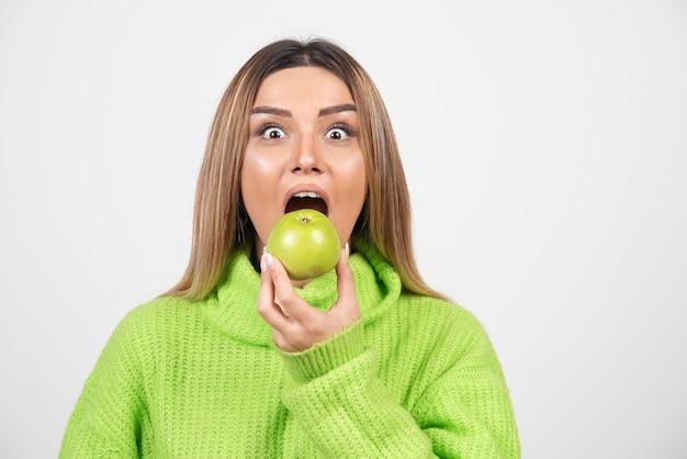 Молодая женщина в зеленой футболке ест яблоко.