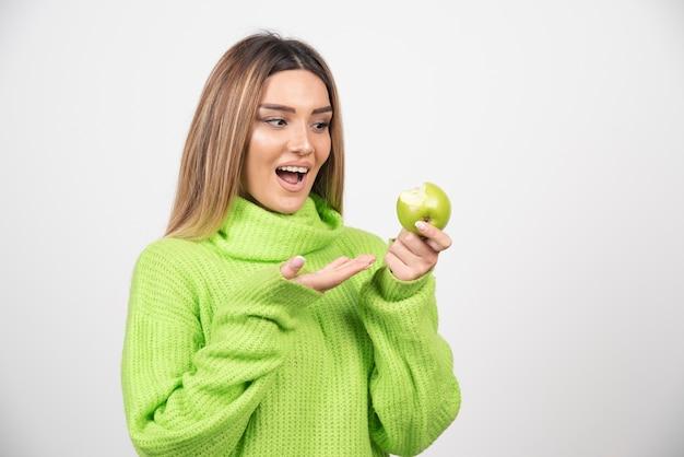 Молодая женщина в зеленой футболке, держащей яблоко.