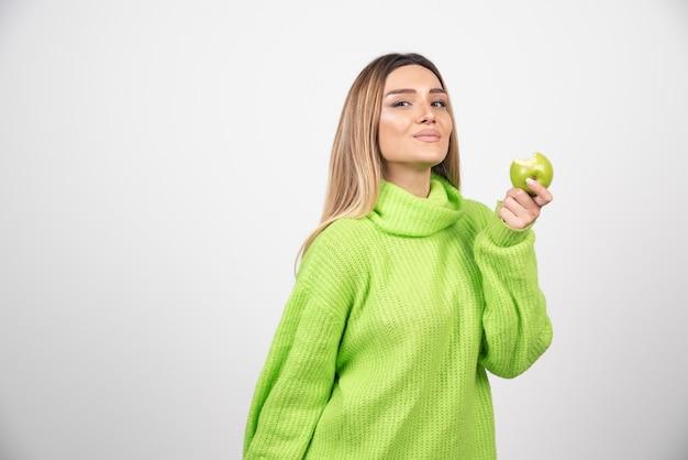 リンゴを持っている緑のtシャツの若い女性