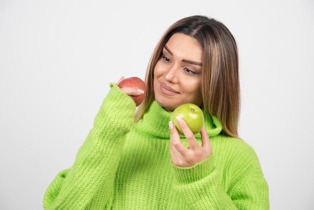 頭上に2つのリンゴを保持している緑のtシャツの若い女性