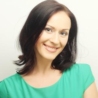 Молодая женщина в зеленой футболке с большой счастливой улыбкой