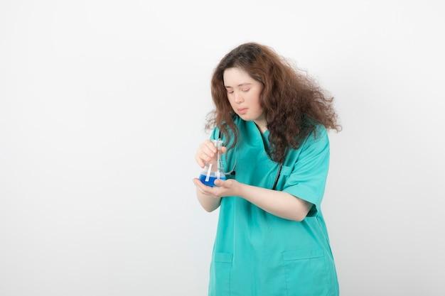파란색 액체가 든 유리병을 들고 녹색 유니폼을 입은 젊은 여성.