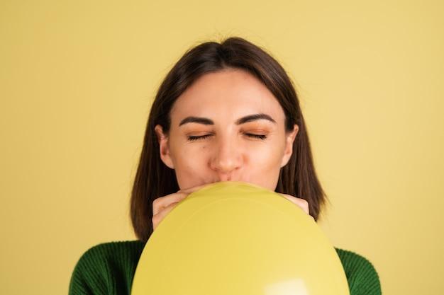 気球を吹く緑の暖かいセーターの若い女性