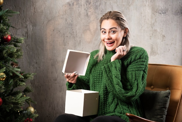녹색 따뜻한 스웨터에 젊은 여자는 선물에 대 한 흥분