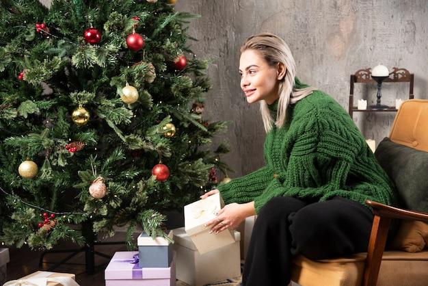녹색 따뜻한 스웨터 앉아서 선물을 들고있는 젊은 여자