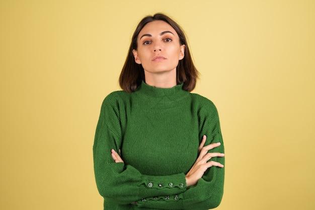 팔짱을 끼고 녹색 따뜻한 스웨터를 입은 젊은 여성