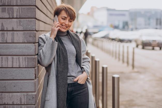 Молодая женщина в сером пальто с помощью телефона