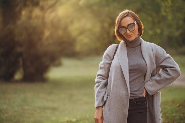 秋の公園を歩く灰色のコートを着た若い女性