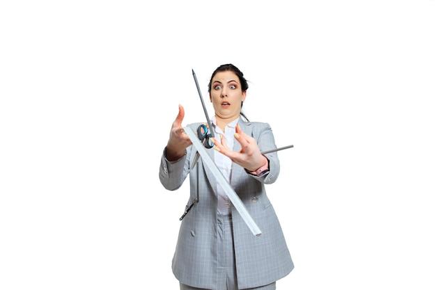 Молодая женщина в сером костюме теряет концентрацию. все идет не так, падает из рук, она пытается это поймать. понятие проблем офисного работника, бизнеса, проблем и стресса.