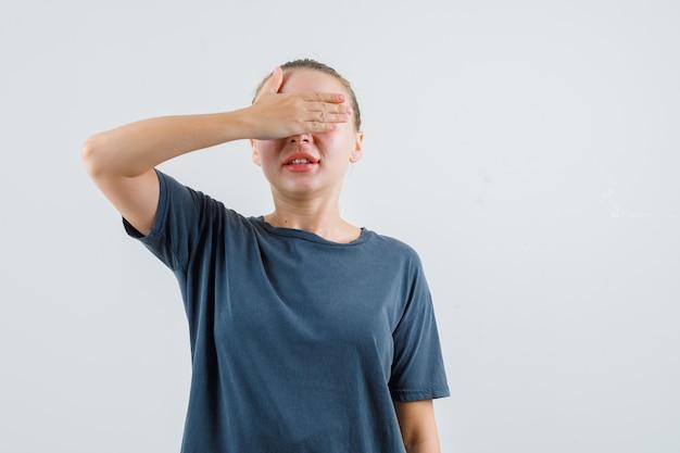 手で目を覆い、興奮して見える灰色のtシャツの若い女性