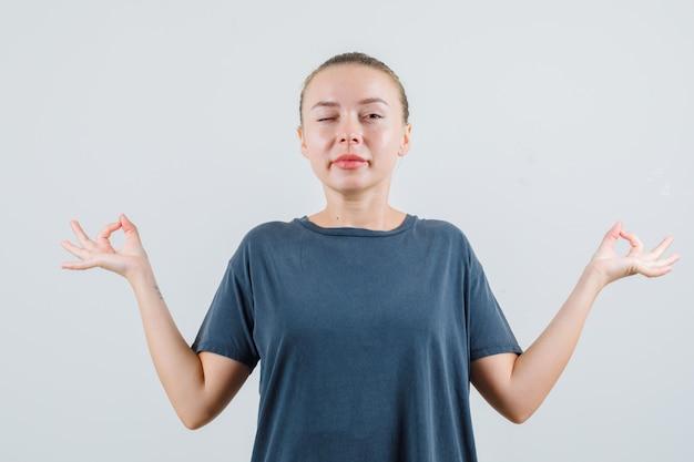 瞑想とまばたきの目をしている灰色のtシャツの若い女性