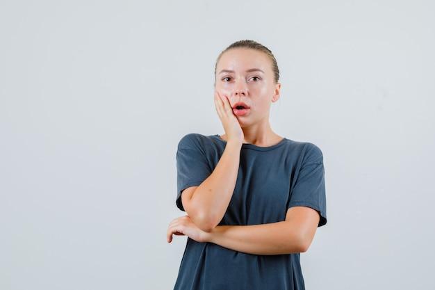 頬に手をつないで、驚いて見える灰色のtシャツの若い女性