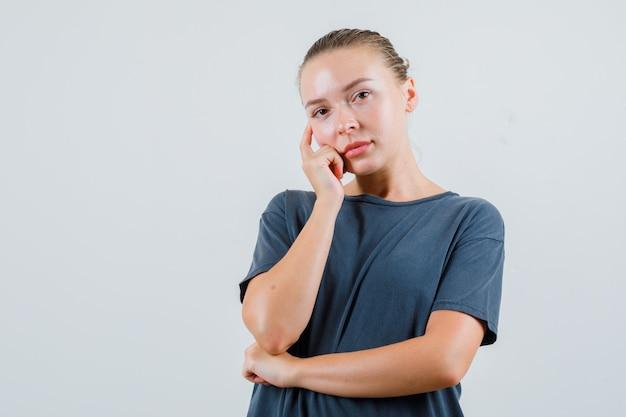 手に頬を傾けて物思いにふける灰色のtシャツの若い女性