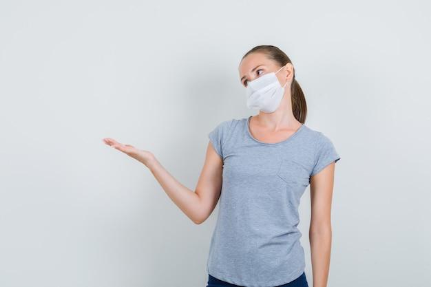 灰色のtシャツ、マスク、手のひらを広げて脇を見ているジーンズ、正面図の若い女性。