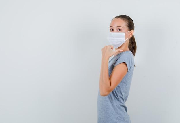 Молодая женщина в серой футболке, маска указывает большим пальцем назад и выглядит позитивно.