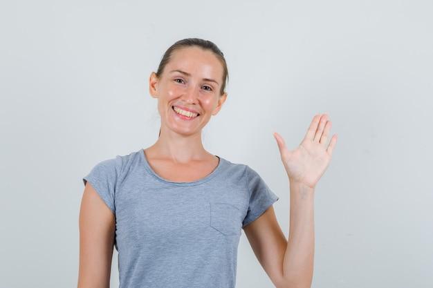 手のひらを示し、陽気に見える灰色のtシャツの若い女性、正面図。