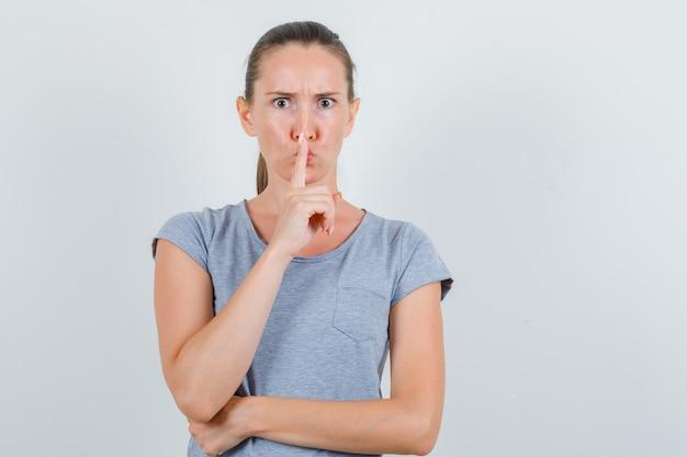 沈黙のジェスチャーを示し、厳格な正面図を示す灰色のtシャツの若い女性。