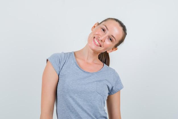 頭を下げながら笑っている灰色のtシャツの若い女性、正面図。