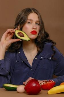 과일의 그룹에 젊은 여자. 건강 관리 및 건강한 영양 개념입니다. 얼굴에 아보카도를 보유