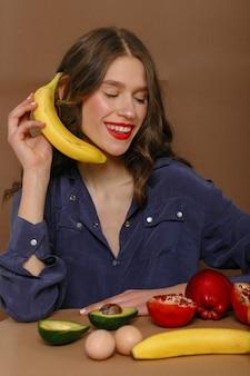 과일의 그룹에 젊은 여자. 건강 관리 및 건강한 영양 개념입니다. 전화처럼 바나나에 sitsspeaks