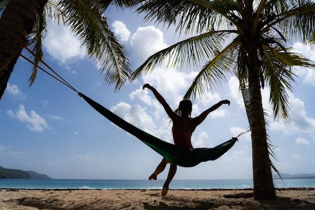Молодая женщина в гамаке, глядя на тропический пляж. Premium Фотографии