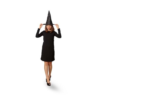 帽子と魔女としてドレスの若い女性