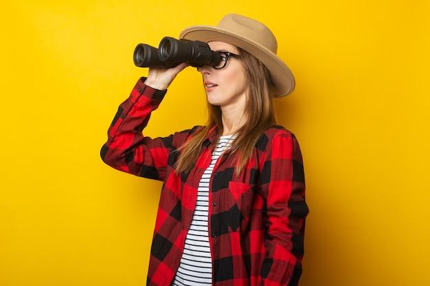 黄色の背景に双眼鏡を通して見ている帽子と格子縞のシャツの若い女性。