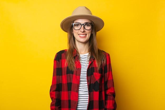 Молодая женщина в шляпе и клетчатой рубашке на желтом.
