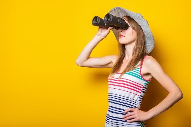 Молодая женщина в шляпе и полосатом платье смотрит в бинокль на желтом пространстве.