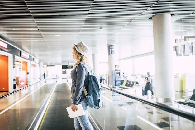 空港でエレベーターで降りる帽子をかぶった若い女性。バックパックを持って、休日の旅行に行くデジタルタブレットを保持している女性。空港でデジタルタブレットを持っている女性の乗客のプロファイル