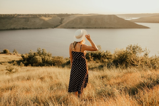 Молодая женщина в шляпе в платье в горошек стоит посреди луга на скале над морем на закате