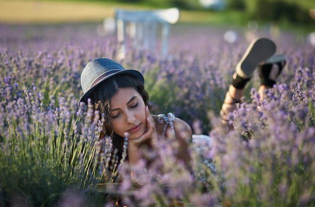 여름날 라벤더 밭에 누워 있는 모자를 쓴 젊은 여자